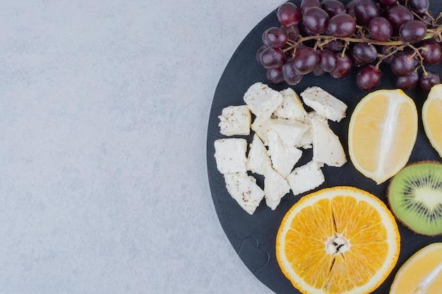 Ein dunkles schneidebrett aus frischen süßen früchten und geschnittenem weißkäse. foto in hoher qualität