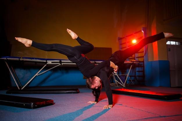Ein duo von akrobaten, das einen doppeltrick vorführt. eine frau im turnanzug und ein mann in sportkleidung. sehr flexible zirkusartisten.
