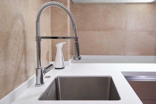 Ein edelstahlspülbecken und ein wasserhahn in einem modernen stil