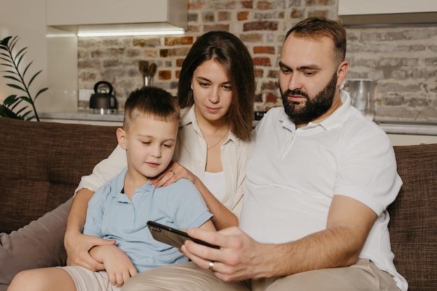Ein ehemann demonstriert die show auf dem smartphone dem lachenden kind und der frau am abend zu hause