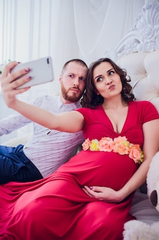 Ein ehemann und eine schwangere frau machen ein selfie, das auf der couch sitzt. sie lieben einander. sie sind zuhause.