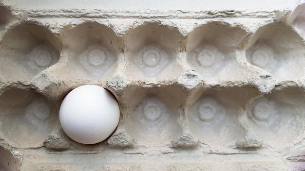Ein ei in einer paketnahaufnahme. einsames hühnerei in einem tablett.