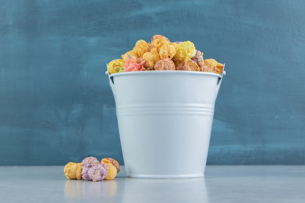 Ein eimer voller süßem buntem popcorn.
