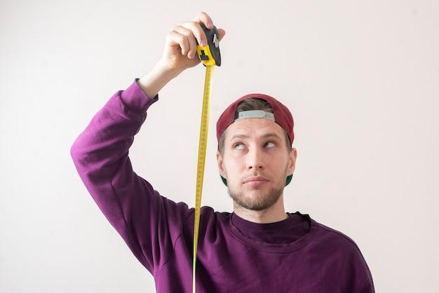 Ein einfacher erwachsener männlicher teenager mit einem rollband misst die höhe an der wand