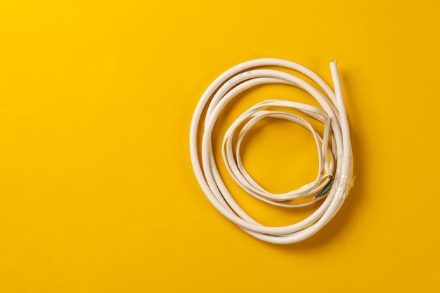 Ein einfaches weißes drahtkabel lag flach auf der bunten oberfläche isoliert, netzwerkverbindungsindustrie