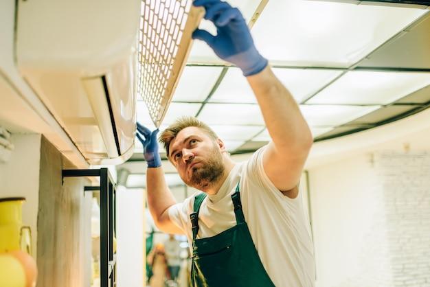 Ein einheitlicher handwerker repariert die klimaanlage