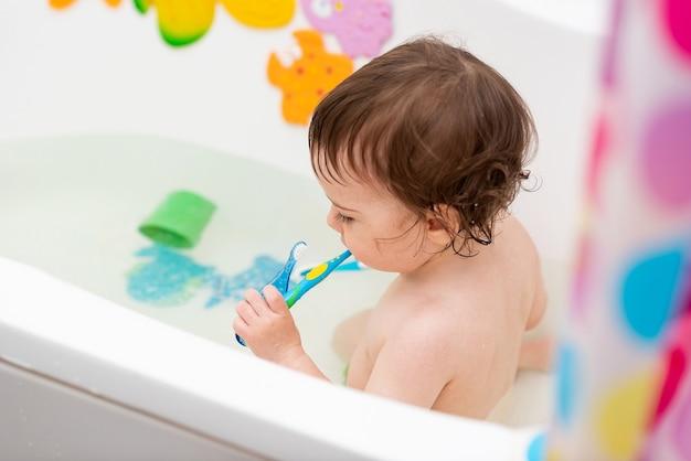 Ein einjähriges baby wäscht sich in der badewanne spielt mit spielzeug und lernt zähneputzen
