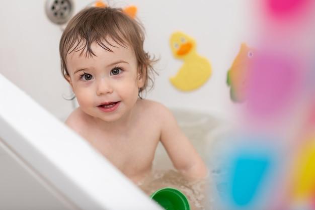 Ein einjähriges baby wäscht sich in der badewanne und spielt mit spielzeug