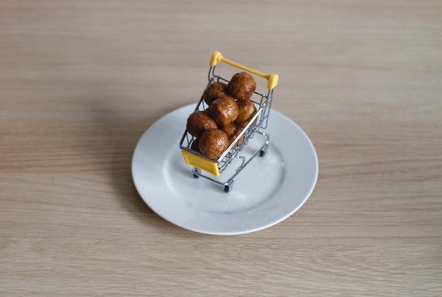 Ein einkaufswagen aus dem supermarkt ist mit fleischbällchen gefüllt. das konzept des lebensmitteleinkaufs