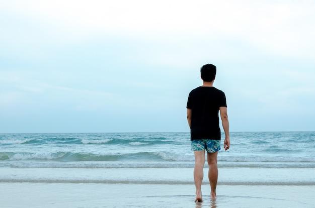Ein einsamer asiatischer mann, der alleine auf strand geht
