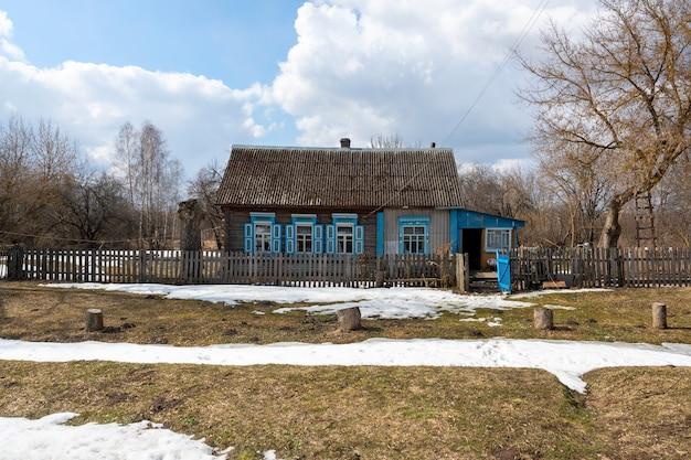 Ein einsames altes haus im dorf mit blauen fensterläden an den fenstern im zeitigen frühjahr. das erwachen der natur. russisches hinterland