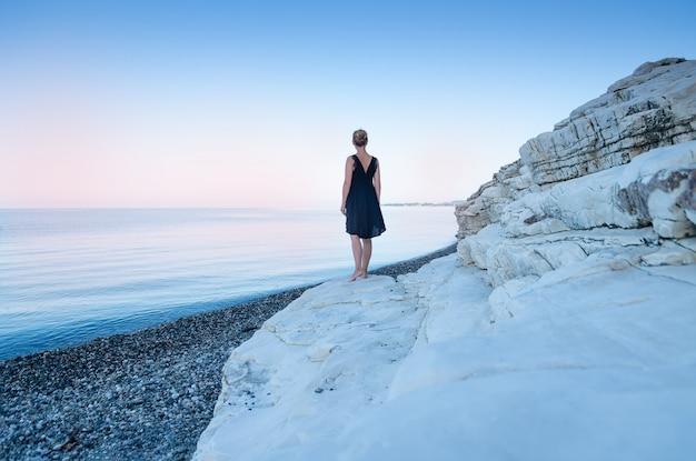 Ein einsames mädchen in einem schwarzen kleid steht an der küste. weiße felsen das konzept des minimalismus.