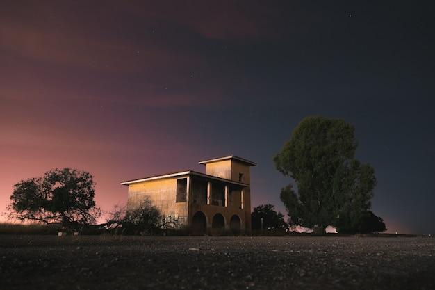 Ein einsames und postapokalyptisches gebäude, umgeben von bäumen in einer dunklen und kalten nacht. langzeitbelichtung fotografie