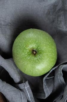 Ein einzelner grüner apfel getrennt auf grau.
