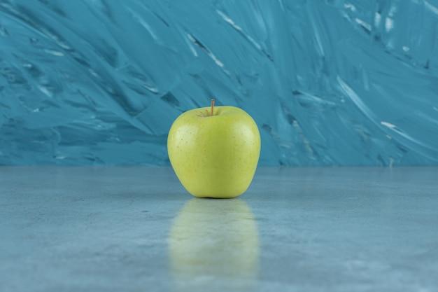 Ein einzelner reifer apfel, auf dem marmorhintergrund.