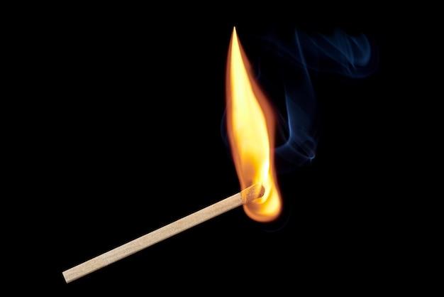Ein einzelnes brennendes streichholz mit flammen und rauch, die isoliert auf einem schwarzen hintergrund aufsteigen