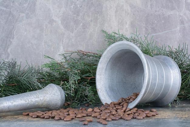 Ein eiseneimer mit kaffeebohnen auf marmorhintergrund. foto in hoher qualität