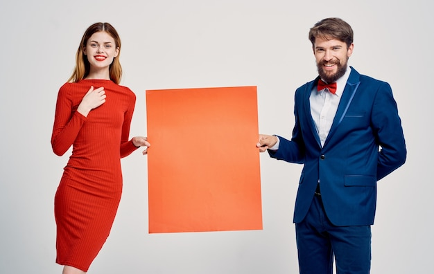 Ein eleganter mann im anzug und eine frau in einem roten kleid mit einer mohnblume in der hand ein plakat für eine werbung Premium Fotos