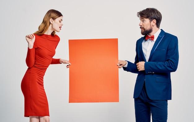 Ein eleganter mann im anzug und eine frau in einem roten kleid mit einer mohnblume in der hand ein plakat für eine