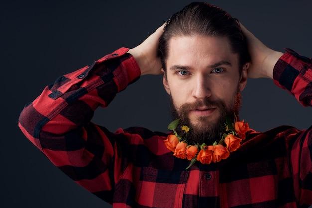 Ein eleganter mann in einem karierten hemd blüht in einem dunklen hintergrund der bartnahaufnahme.