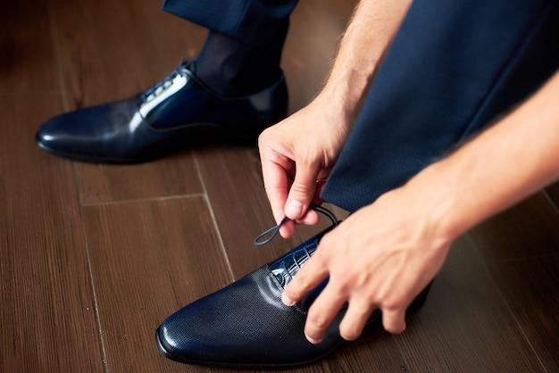 Ein eleganter mann zieht schwarze formelle lederschuhe an. schuhe binden.