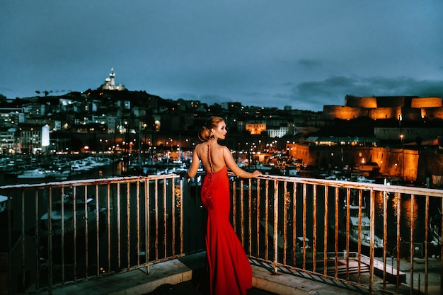 Ein elegantes mädchen in einem roten abendkleid auf den straßen der nachtstadt marseille. eine frau in einem roten abendkleid in frankreich.