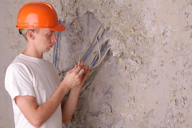 Ein elektriker, der in einem reparaturhaus arbeitet