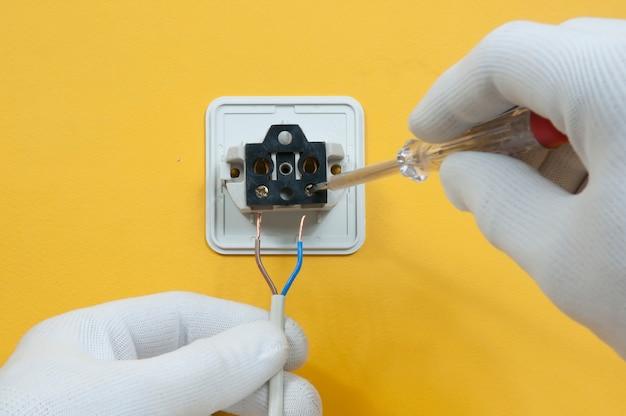 Ein elektriker in weißen handschuhen schraubt drähte an eine steckdose an einer gelben wand, draufsicht, nahaufnahme