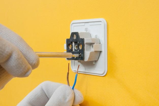 Ein elektriker in weißen handschuhen schraubt drähte an eine steckdose an einer gelben wand
