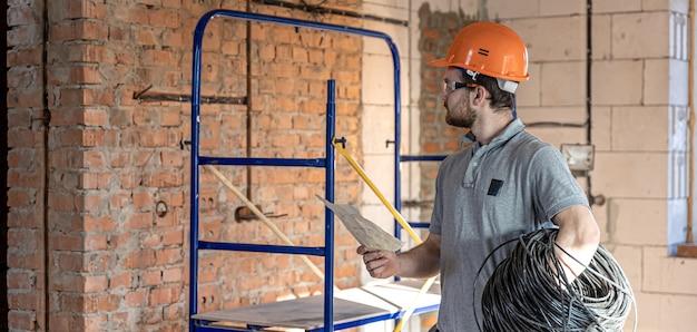 Ein elektriker untersucht eine konstruktionszeichnung, während er auf einer baustelle ein elektrisches kabel in der hand hält.