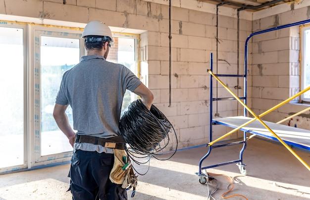 Ein elektriker untersucht eine konstruktionszeichnung, während er auf einer baustelle ein elektrisches kabel in der hand hält