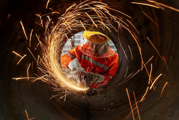 Ein elektrisches radschleifen bei industriearbeitern, die metallrohre mit vielen scharfen funken schneiden