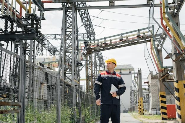 Ein elektrotechniker inspiziert hochspannungsgeräte an einem umspannwerk.
