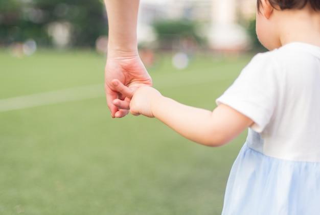 Ein elternteil hält die hand eines kleinen kindes