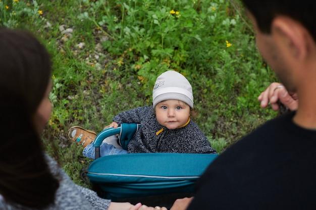 Ein elternteil schiebt einen kinderwagen auf einem bewaldeten weg. baby in einem kinderwagen schaut eltern an. junge in einer warmen strickjacke, die in einem modernen kinderwagen für einen spaziergang im park sitzt