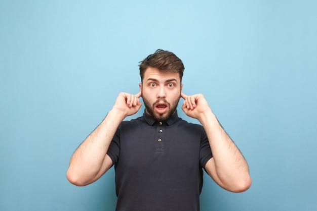Ein emotionaler mann mit einem überraschten gesicht schließt die ohren mit den auf blau isolierten fingern