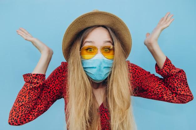Ein emotionales mädchen in einem roten kleid, hut und einer medizinischen maske auf blauem hintergrund. reise wegen coronavirus-epidemie abgesagt.