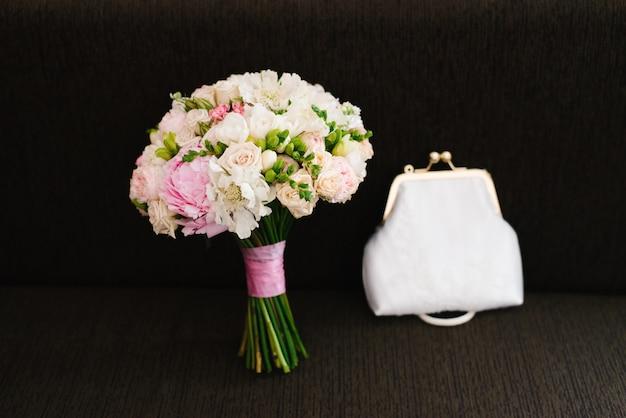 Ein empfindlicher und schöner hochzeitsblumenstrauß und eine weiße tasche auf einem dunkelbraunen hintergrund. zubehör braut bei der hochzeit