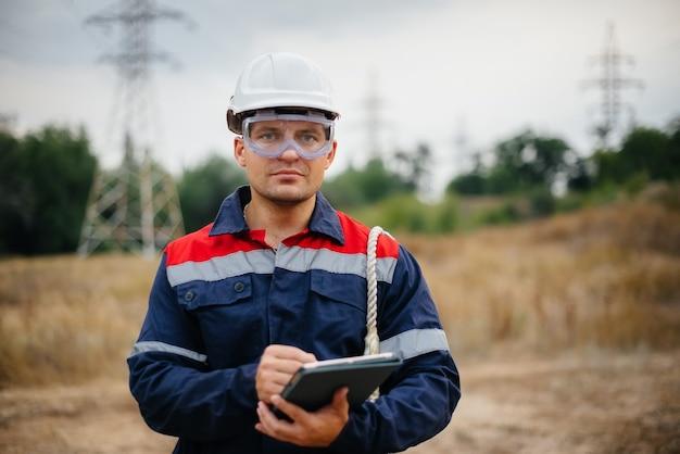 Ein energiearbeiter inspiziert stromleitungen. energie.