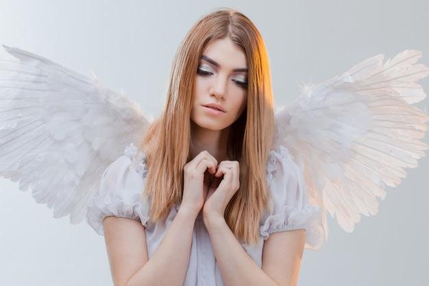 Ein engel vom himmel hält etwas auf den handflächen. junges, wundervolles blondes mädchen im bild eines engels mit weißen flügeln.