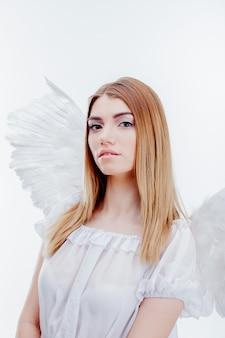 Ein engel vom himmel. junges, wundervolles blondes mädchen im bild eines engels mit weißen flügeln. porträt nahaufnahme