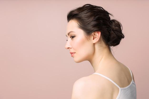 Ein enges porträt einer schönen frau mit perfekter haut, isoliert auf rosa hintergrund, das konzept von