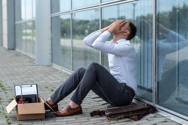 Ein entlassener büroangestellter sitzt auf dem boden in der nähe eines modernen bürogebäudes. der mann ist sehr besorgt über die entlassung. der arbeiter bedeckte sein gesicht mit den händen.