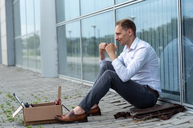 Ein entlassener büroangestellter sitzt auf dem boden in der nähe eines modernen bürogebäudes. der mann ist sehr besorgt über die entlassung. der mitarbeiter ist sehr wütend.