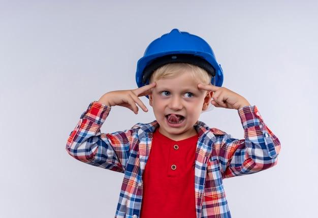 Ein entzückender niedlicher kleiner junge mit blondem haar, der kariertes hemd im blauen helm trägt und mit zeigefingern auf seinen kopf zeigt