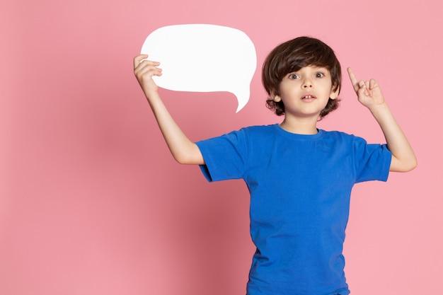 Ein entzückender süßer junge des vorderansichtskindes im blauen t-shirt, das weißes zeichen auf dem rosa raum hält