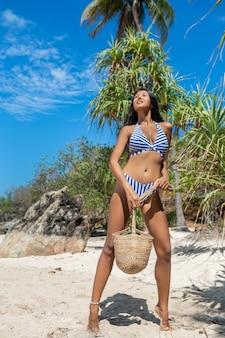 Ein entzückender tropischer asiatischer brunette in einer bikini- und weidentasche, die auf dem strand aufwirft.