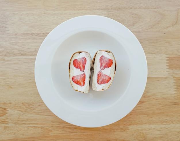 Ein erdbeer-schlagsahne-sandwich in einem weißen teller