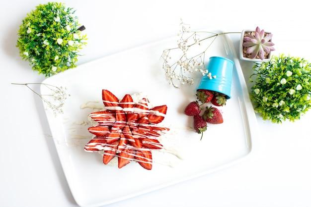Ein erdbeerkuchen der draufsicht mit geschnittenen frischen erdbeeren, die mit sahne zusammen mit ganzen erdbeeren innerhalb des weißen schreibtischfruchtbeerenzuckers verziert werden