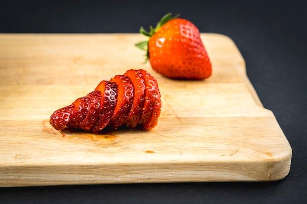 Ein erdbeerschnitt auf einem holz, rezept für hausgemachte erdbeeren